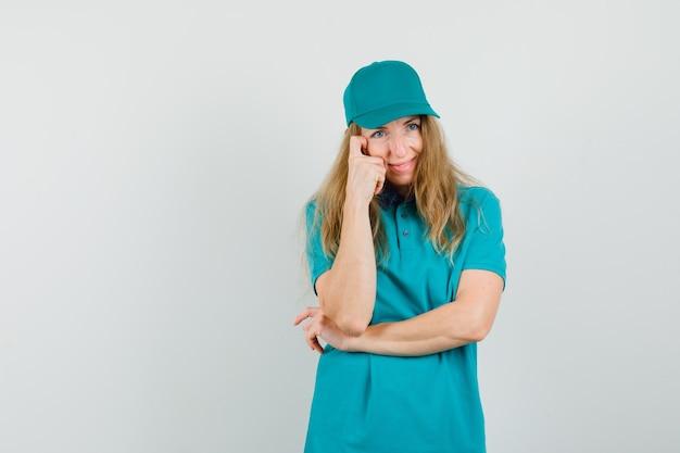 Tシャツの配達の女性、キャップは思考のポーズで立って、陽気に見える