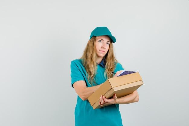 Tシャツの配達の女性、段ボール箱にクリップボードに書き込むキャップ