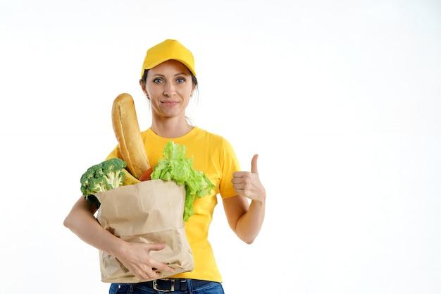 黄色の食料品の袋を押しながら親指をあきらめて配達の女性