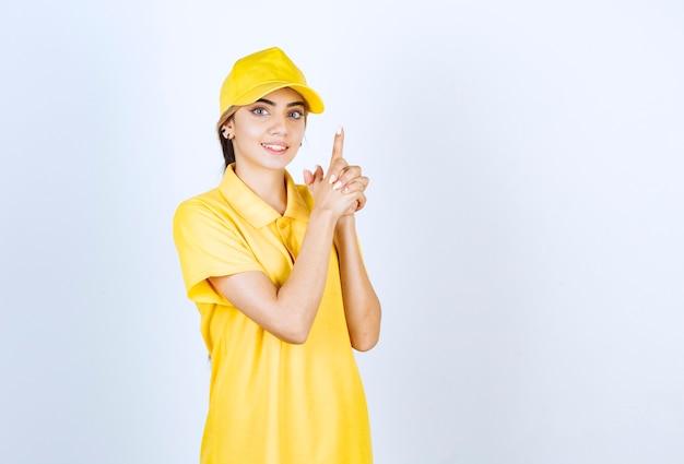 권총처럼 손가락을 들고 노란색 유니폼에 배달 여자.