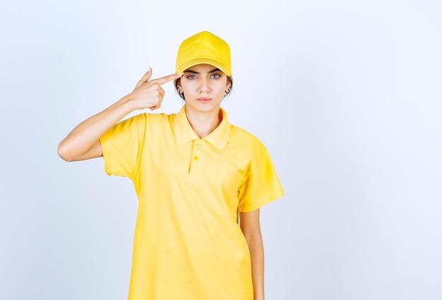 노란색 제복을 입은 배달 여성이 권총처럼 관자놀이 근처에서 한 손가락을 들고 있습니다.