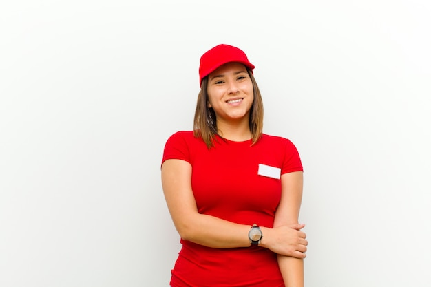 Delivery woman laughing shyly and cheerfully, with a friendly and positive but insecure attitude against white background