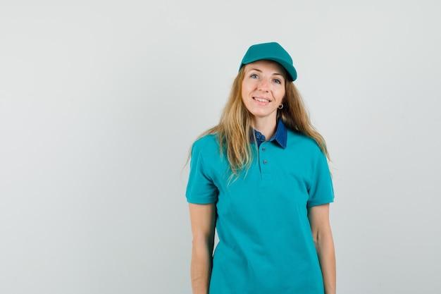 Женщина доставки смотрит на камеру в футболке, кепке и выглядит веселой.