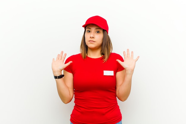 """Delivery woman looking nervous, anxious and concerned, saying not my fault or i didnã¢â€âšãƒâ""""ãƒâ´t do it against white"""