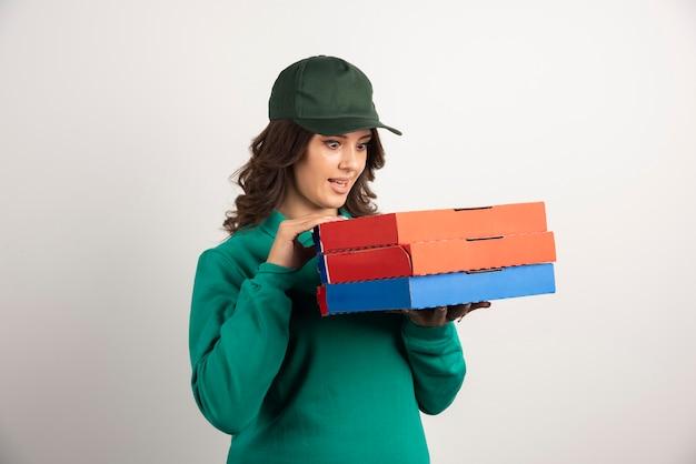 Donna di consegna guardando scatole per pizza con espressione sorpresa.