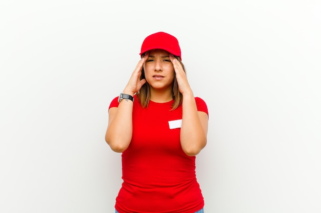 Delivery woman looking stressed and frustrated, working under pressure with a headache and troubled with problems against white