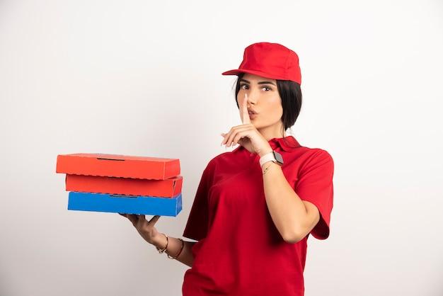 Donna di consegna che fa segno di silenzio mentre si tiene la pizza.