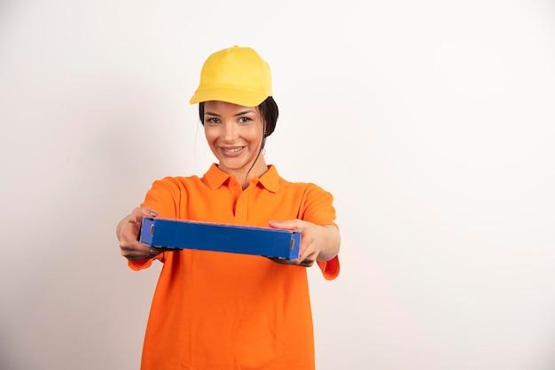 Donna di consegna che offre un cartone di pizza sulla parete bianca.