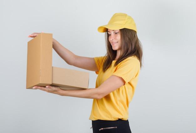 Donna di consegna che apre la scatola di cartone in maglietta gialla, pantaloni, berretto e che sembra felice