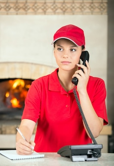 Delivery woman of pizza is taking orders by phone.
