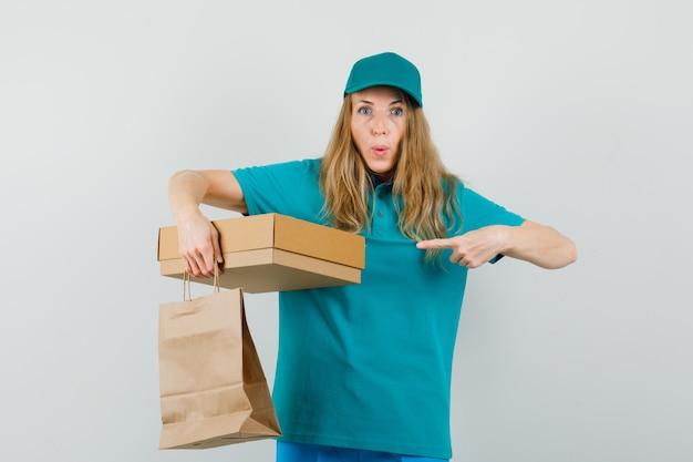 Женщина-доставщик, указывая на картонную коробку и держа бумажный пакет в футболке, кепке и глядя с любопытством.
