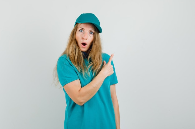 Delivery woman pointing away in t-shirt, cap and looking surprised