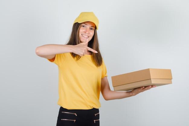 Доставщик показывает пальцем на картонную коробку в футболке, брюках, кепке и выглядит весело