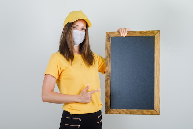 Delivery woman pointing finger at blackboard in t-shirt, pants, cap and mask and looking glad.