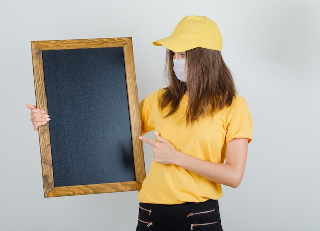 Delivery woman pointing finger at blackboard in t-shirt, pants, cap and mask