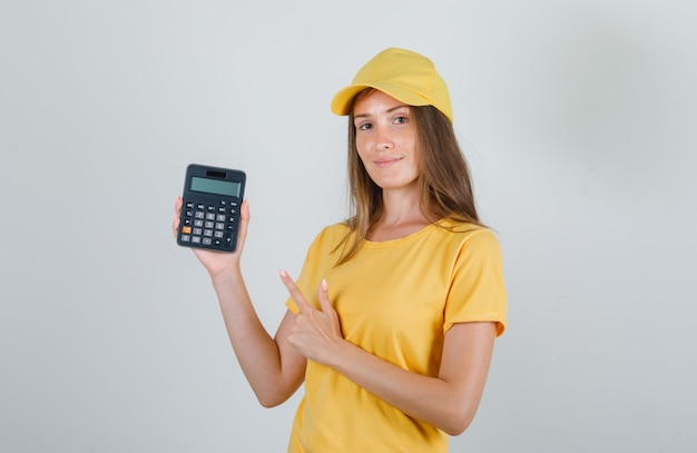 Delivery woman pointing finger at calculator in t-shirt, cap and looking cheerful