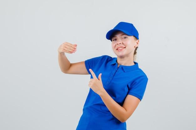 Donna di consegna che indica le sue dita piegate in maglietta blu e cappello e che sembra divertente