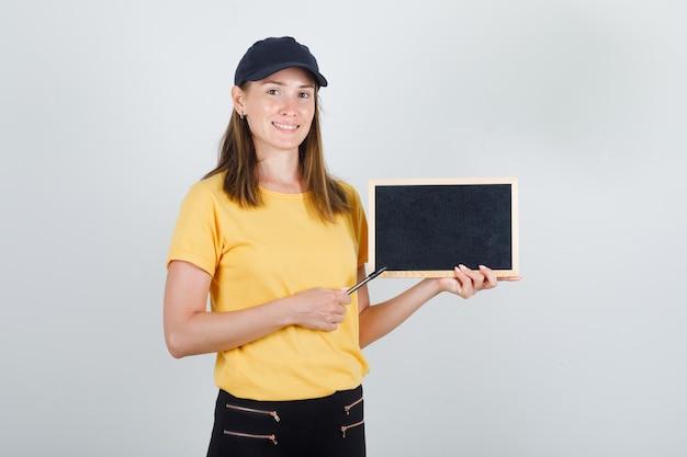 배달 여자 t- 셔츠, 바지, 모자에 칠판에 펜을 가리키는 기쁜 찾고.