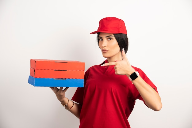 Delivery woman pointing at pizza boxes.