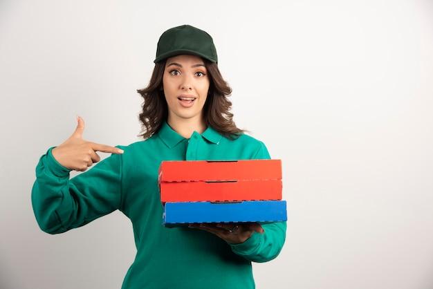 Donna di consegna che indica alle scatole della pizza.