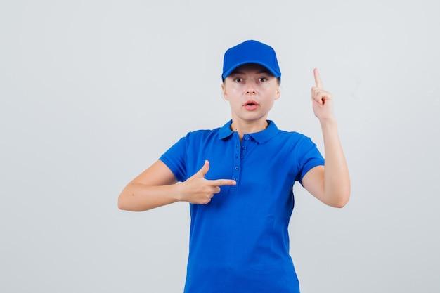 Donna di consegna che punta a lato con il dito in alto in maglietta blu e berretto e sembra seria