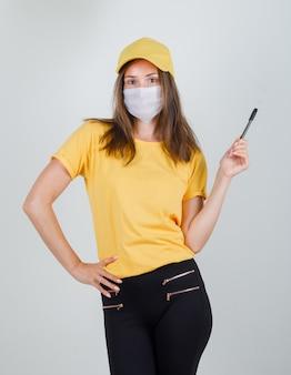 Tシャツ、ズボン、キャップ、マスクでペンを保持しながらポーズをとる配達女性