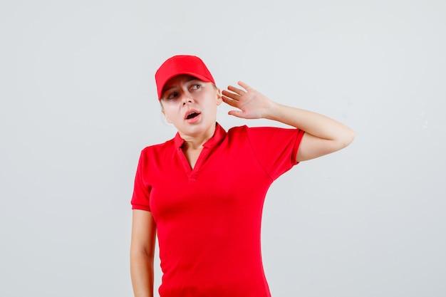 Женщина-доставщик поднимает руку в защитной манере в красной футболке и кепке и выглядит испуганной