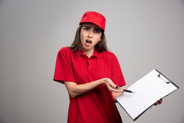 Donna di consegna in uniforme rossa che ha problemi.