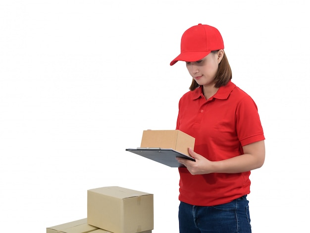 Delivery woman in red uniform with parcel boxes making notes on delivery receipt clipboard, isolated on white