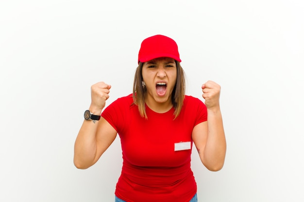 Delivery woman shouting aggressively with an angry expression or with fists clenched celebrating success against white