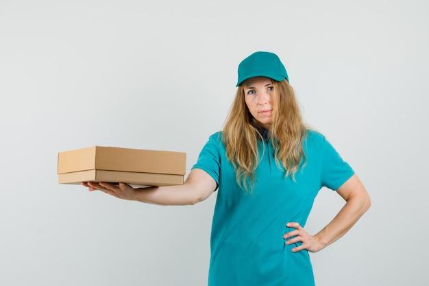 Доставка женщина показывает картонную коробку в футболке, кепке