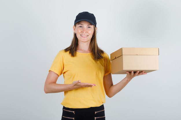 Delivery woman showing cardboard box in t-shirt, pants, cap and looking jolly