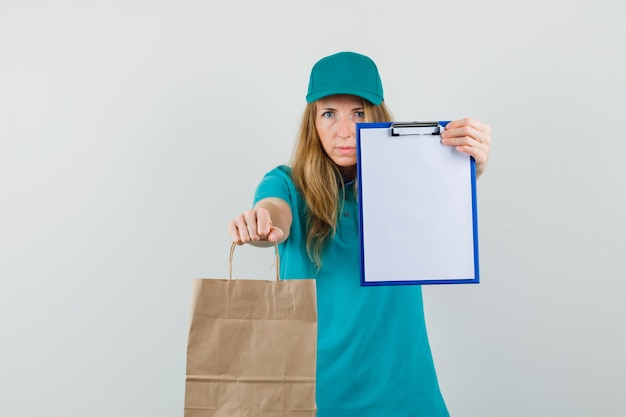 Tシャツ、キャップでクリップボードと紙バッグを示す配達の女性