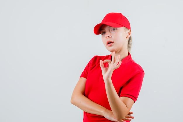 Donna di consegna che mostra gesto giusto in maglietta rossa e cappuccio e che sembra soddisfatta