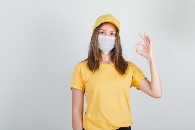 Donna di consegna che mostra gesto giusto in maglietta, pantaloni, berretto e maschera e sembra contenta.