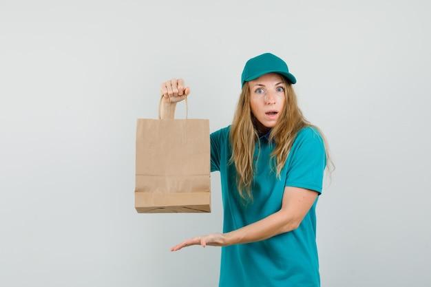 Женщина-доставщик показывает бумажный пакет в футболке, кепке и выглядит удивленным.