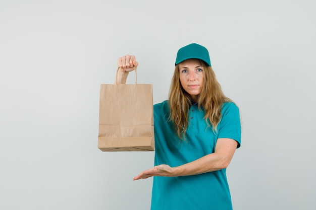 Delivery woman showing paper bag in t-shirt, cap