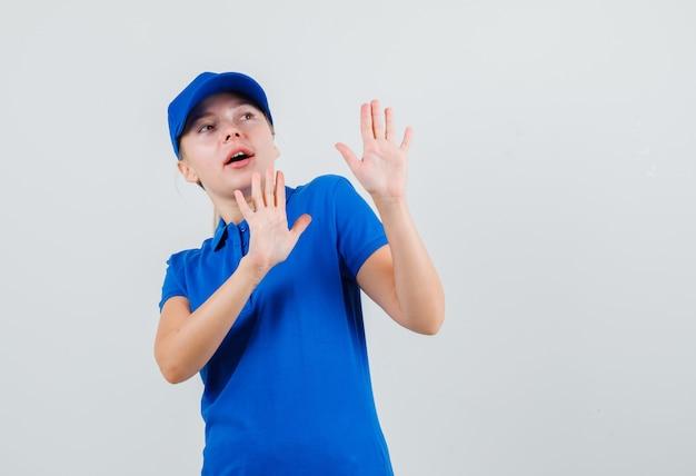 Donna di consegna che mostra il gesto di arresto in maglietta blu e cappello e che sembra spaventata
