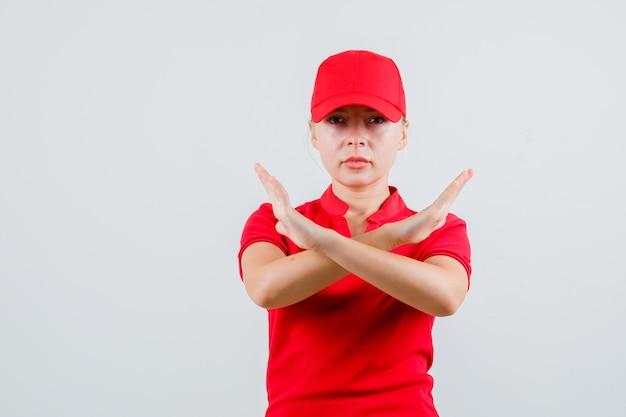 Donna di consegna che mostra il gesto di arresto in maglietta rossa e berretto e sembra rigorosa