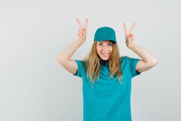 Delivery woman showing v-sign in t-shirt, cap and looking funny.