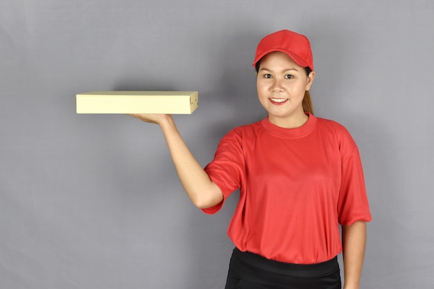 Delivery woman smiling and holding a pizza box