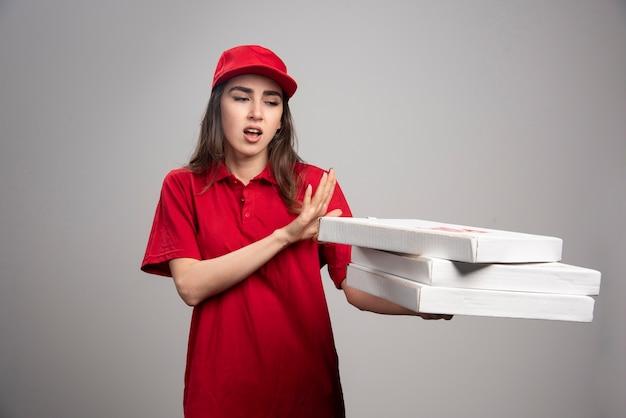 ピザの箱から離れて立っている配達の女性。