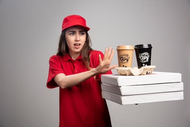Donna di consegna in piedi lontano da pizza e tazze di caffè.