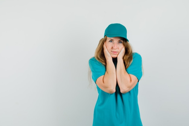 Delivery woman in t-shirt, cap clasping face with hands and looking pretty