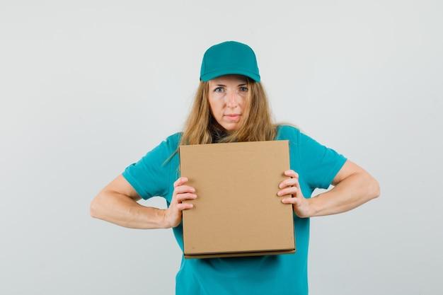 Donna di consegna in t-shirt, cappuccio che tiene scatola di cartone