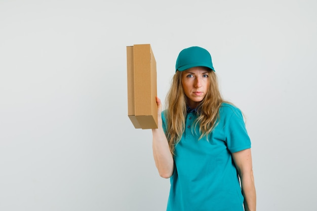 Delivery woman in t-shirt, cap holding cardboard box