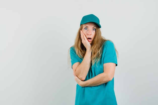 Delivery woman in t-shirt, cap holding hand on cheek and looking shocked
