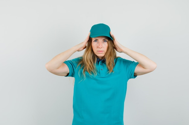Donna delle consegne in t-shirt, berretto che tiene le mani alla testa e sembra stanca