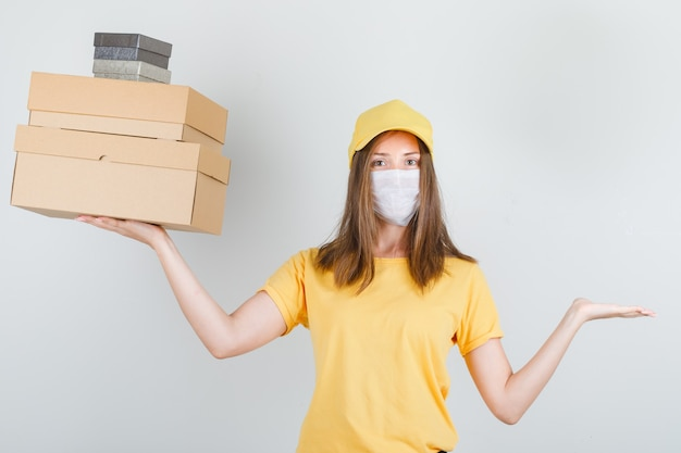 Delivery woman in t-shirt, cap, mask holding boxes with hand gesture