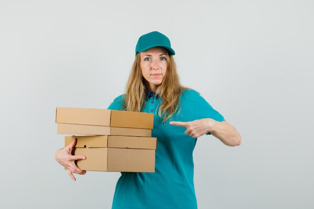 Delivery woman in t-shirt, cap pointing at cardboard boxes and looking confident
